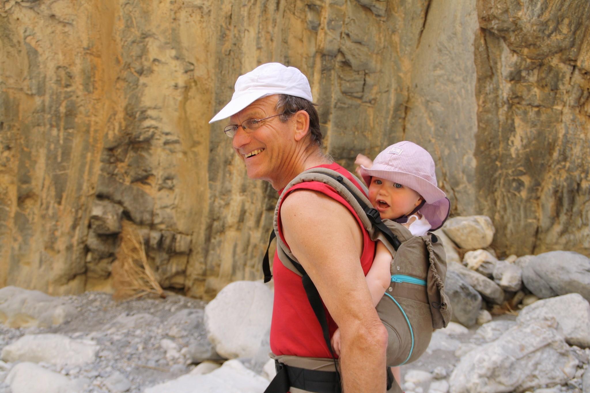 Baby bij opa op de rug in draagzak