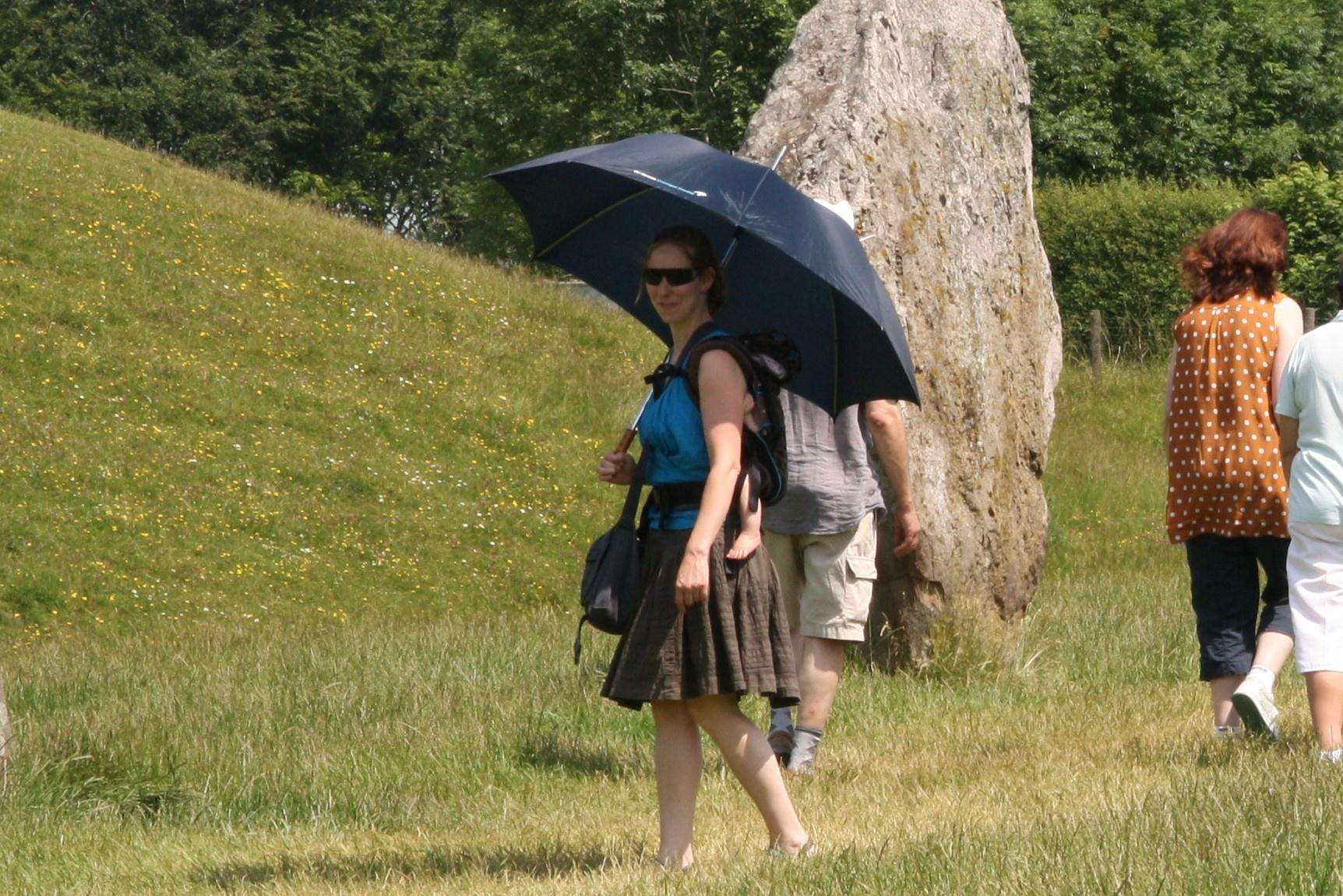 vrouw met baby in draagzak onder paraplu