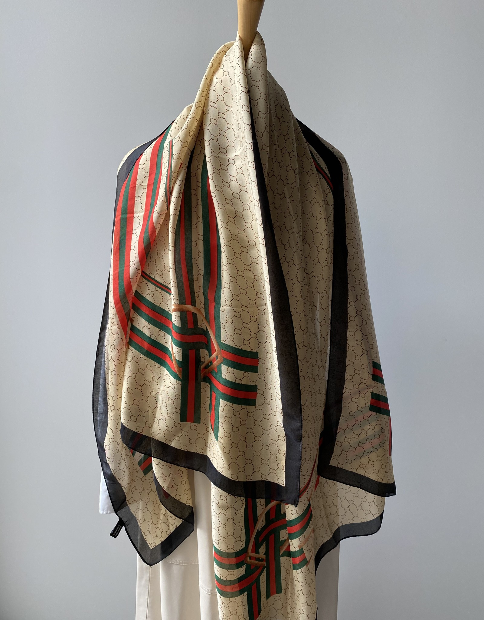 Long scarf with C logo in beige, red, green and black.