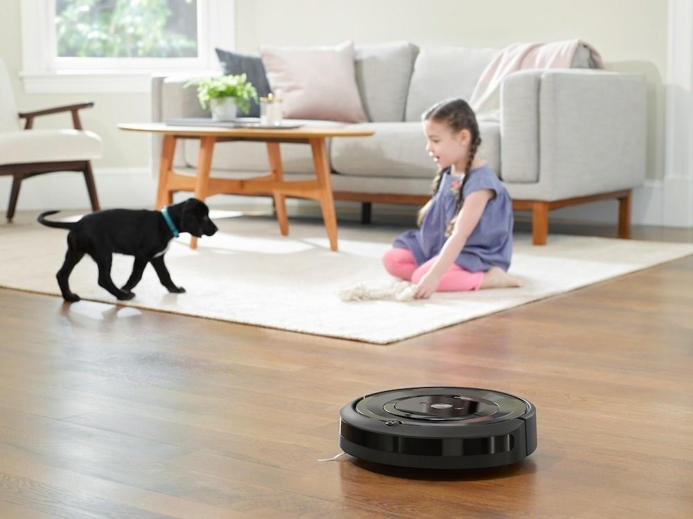 Roomba e5 is aan het werk in een huiskamer waar ook een meisje op een wit vloerkleed met een zwarte pup speelt.