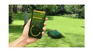 mobiele telefoon met de robomow app vastgehouden door een hand boven een grasveld waar een robomow rijdt