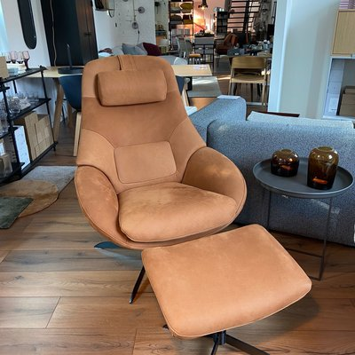 Bolia Saga Armchair with return swivel function with footstool and headrest - Austin Leather, Black Lacquered Steel, Cognac