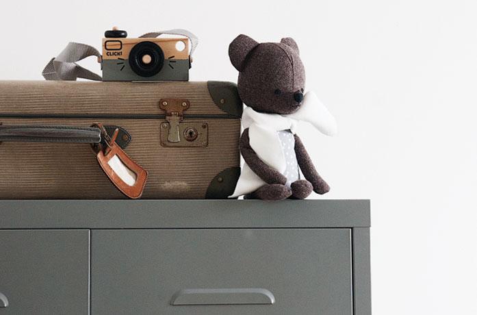 Knuffelbeer en houten speelgoedcamera op kast