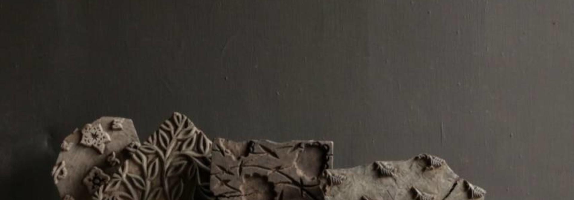 Hölzerner Batikstempel auf einem Eisenfuß