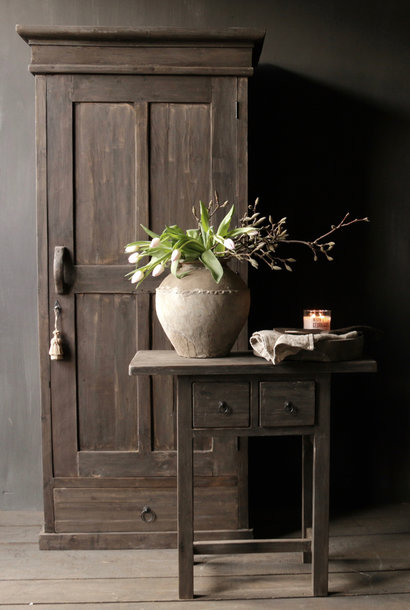 Tough massive door cabinet made of old wood with a drawer
