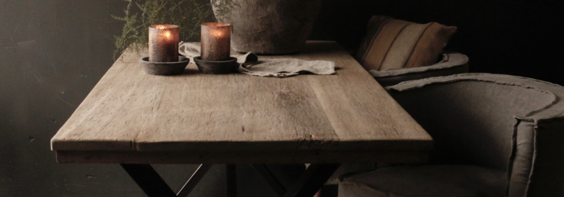 Aged brushed dining room table made of old wood with an iron cross frame