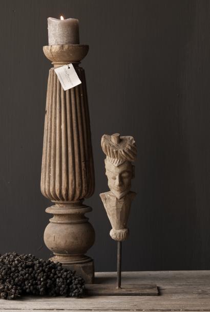 Alte graue Holzfigur auf eisernem Fuß
