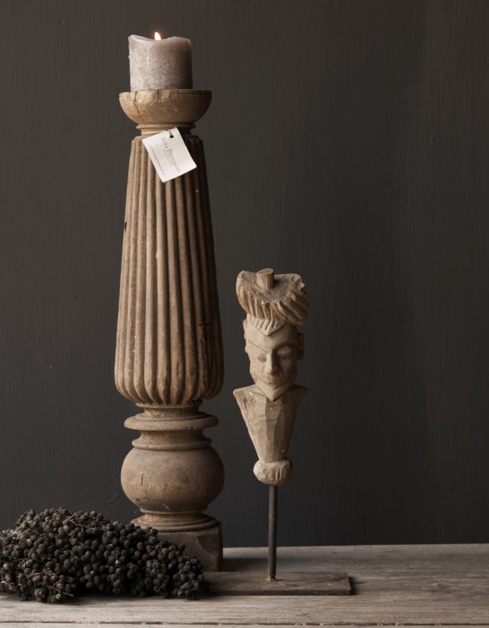 Alte graue Holzfigur auf eisernem Fuß-1