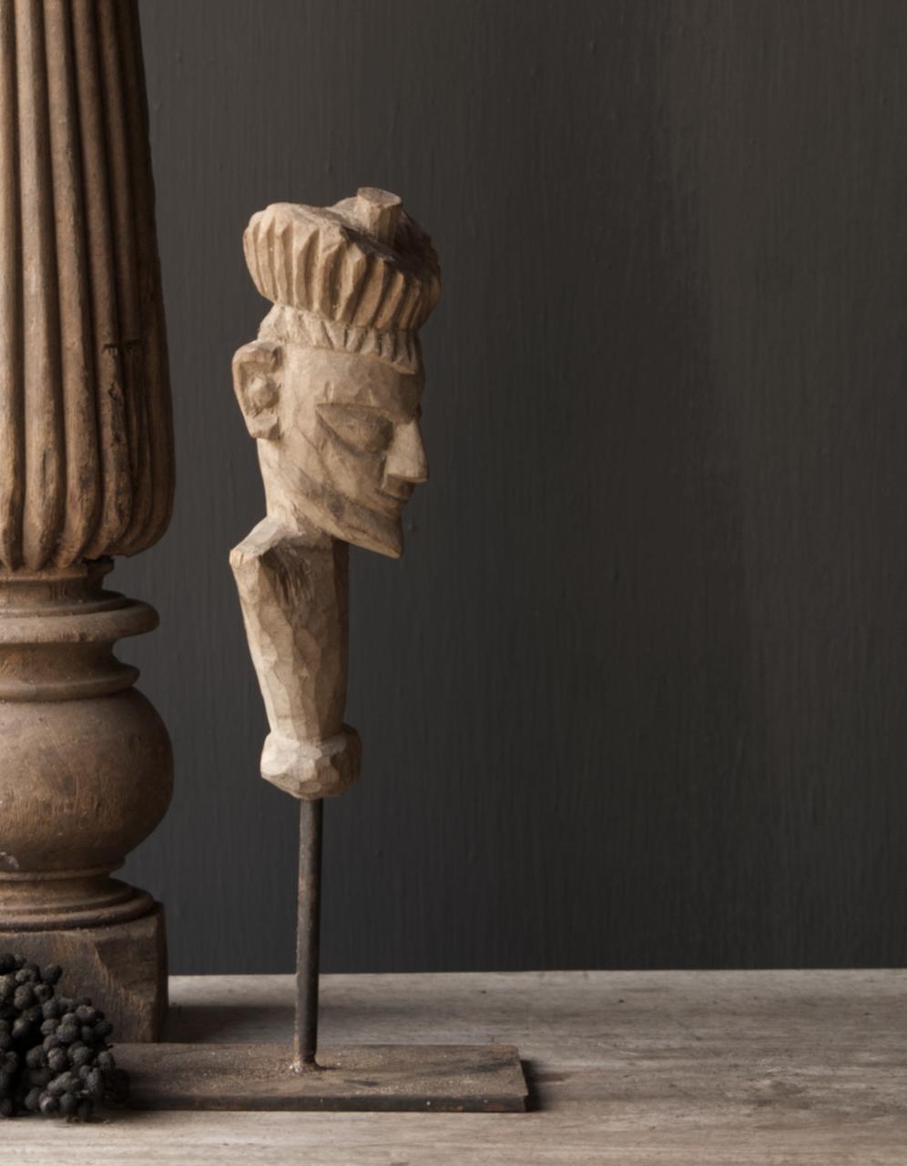 Alte graue Holzfigur auf eisernem Fuß-2