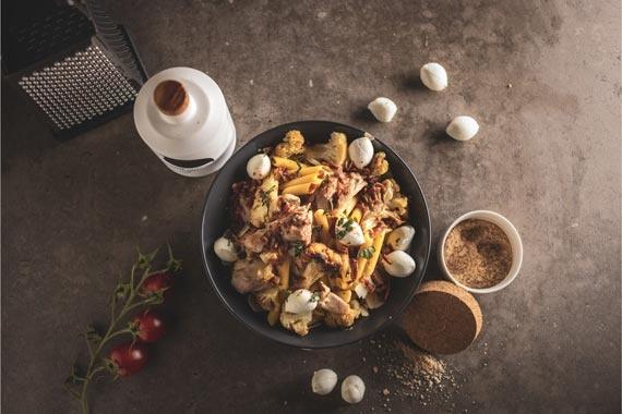 Penne pasta met kipfilet, krokante bloemkool, mozzarella en spekjes