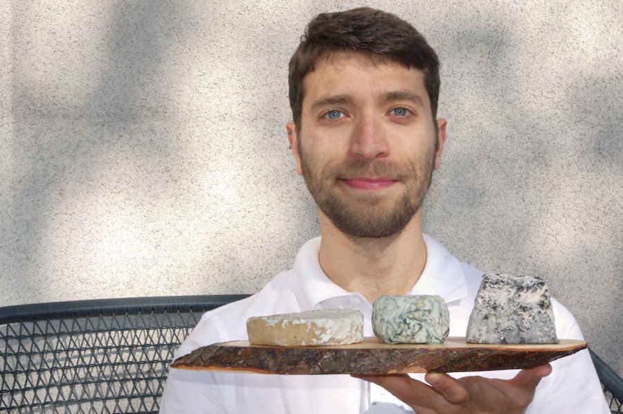 Anderson Santos founder holding vegan cheeses