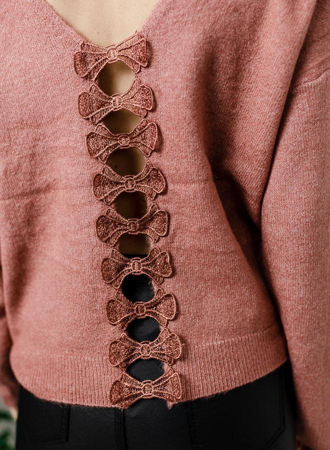 Oudroze trui met strikjes op rug