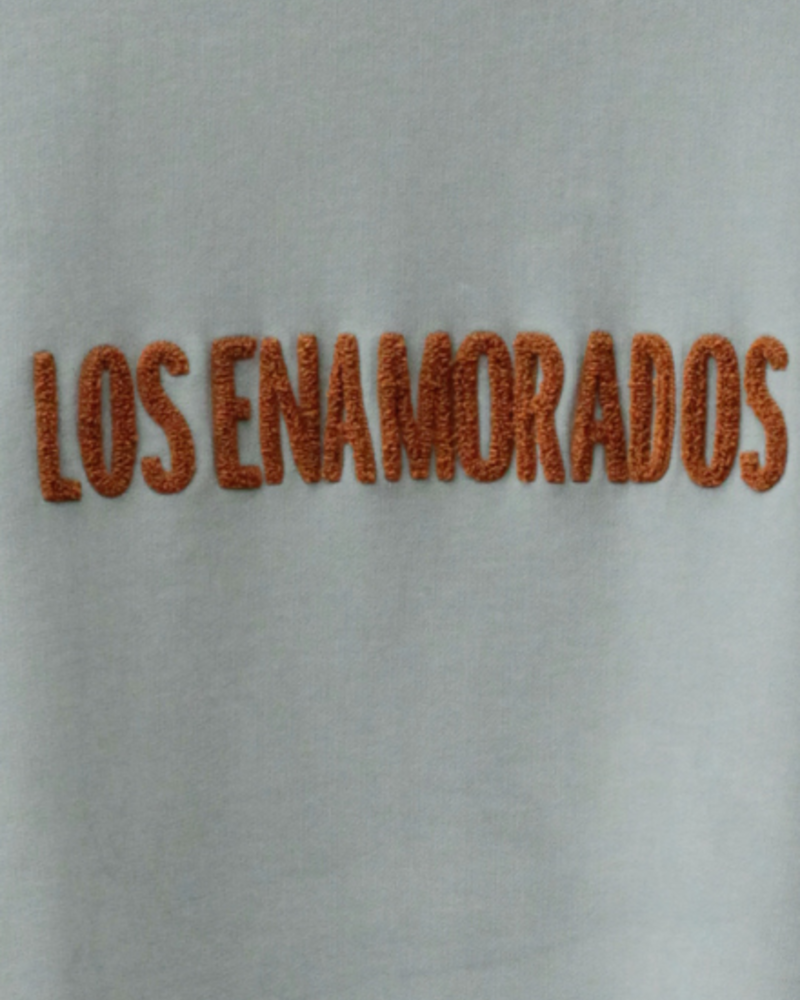 Los Enamorados Embroidered Light Blue  Sweater with Bronze Logo