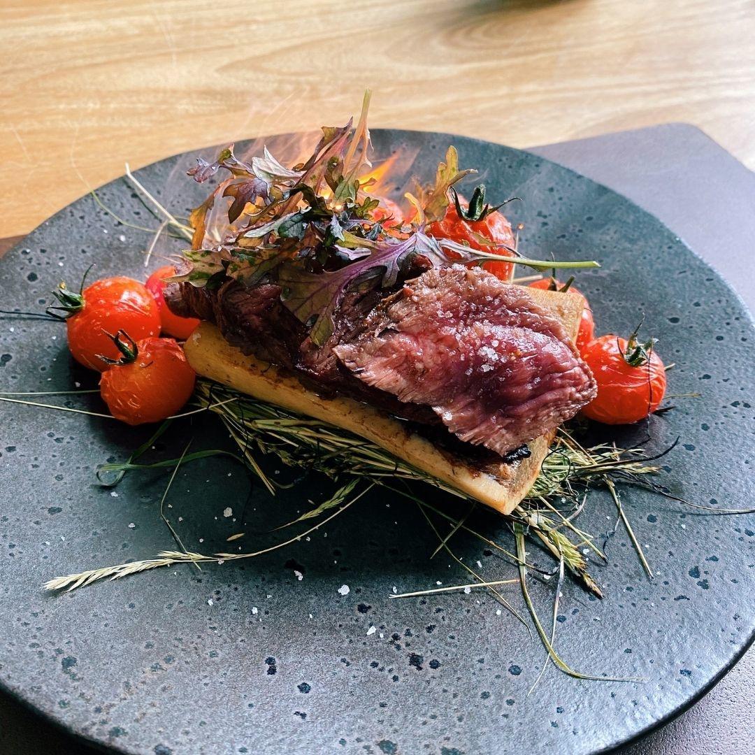 Rubia Gallega Presa steak met mergpijp gegaard op hooi en geroosterde tomaten