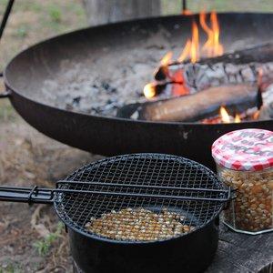 Bij Heldere Hemel Popcorn maken boven een vuurtje.