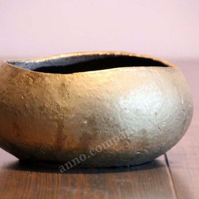 Goudkleurige schaal van aardewerk met een unieke uitstraling