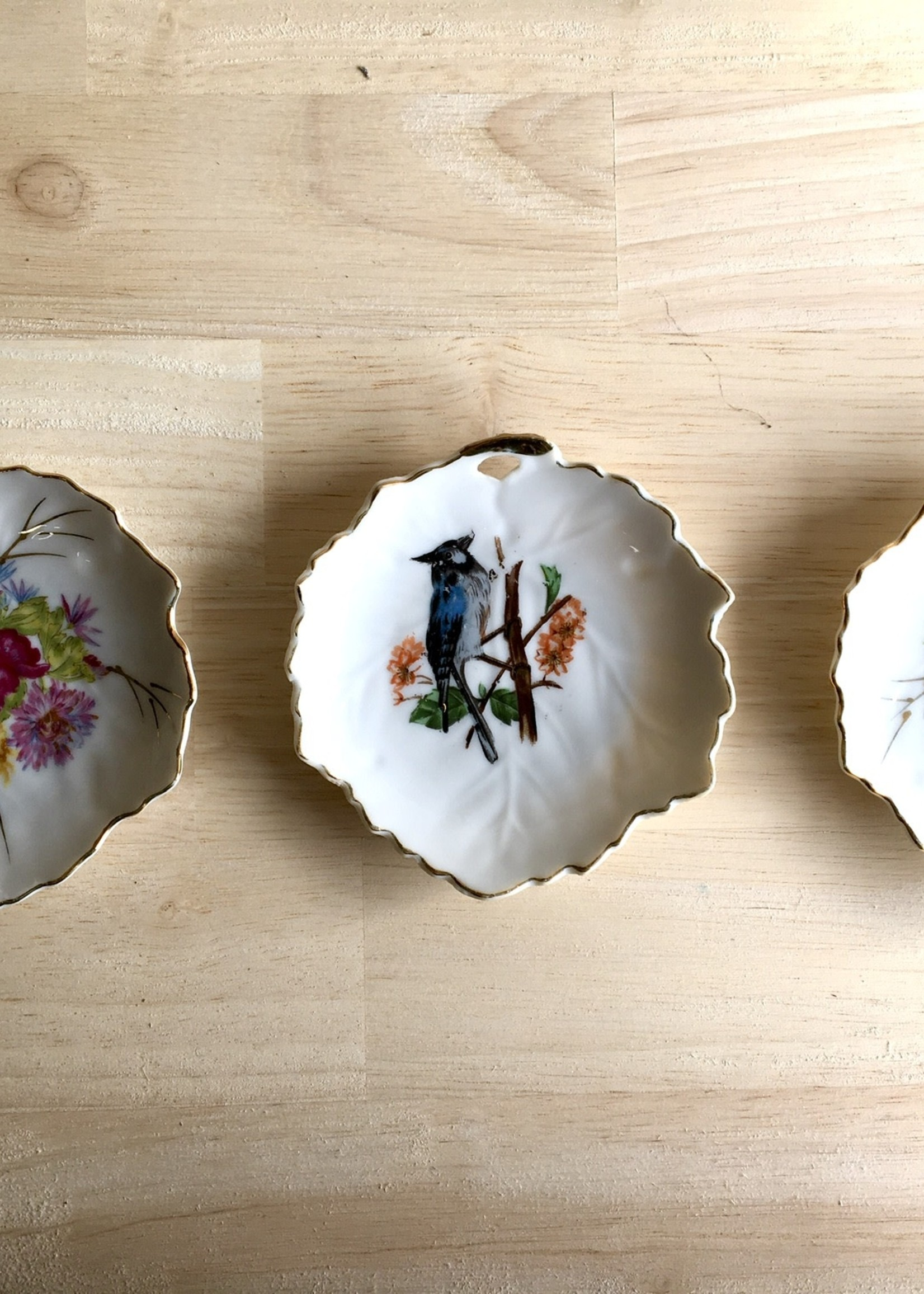 Mini Porcelain cups in leaf shape with rim, two with gold floral decoration and one with bird decoration
