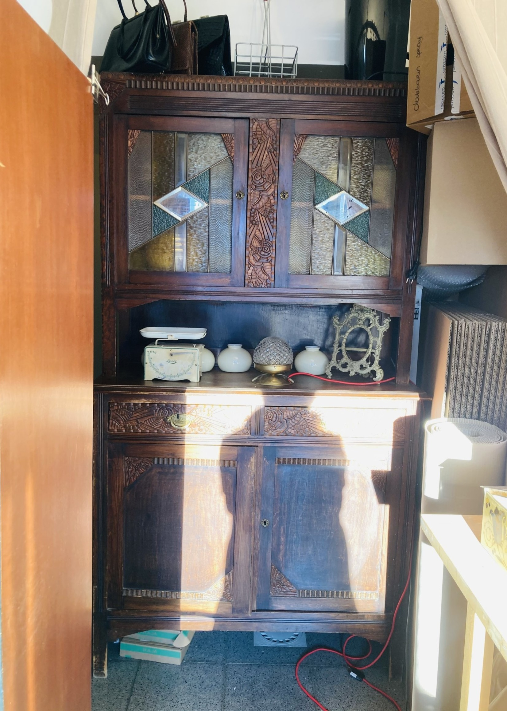 Highboard/kitchen cabinet with carved woodwork and green glass in lead doors
