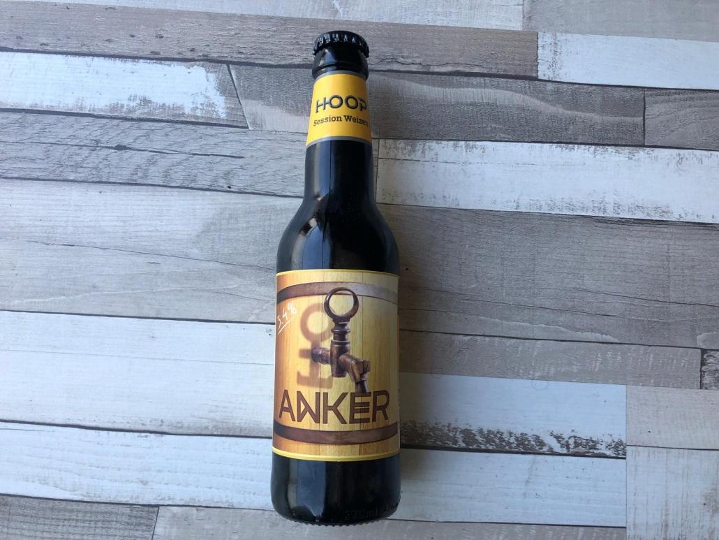 """Anker  Herkomst: Zaandijk, Nederland  Een Session Weizen met een redelijk helder okergele kleur. In de neus herken je de geur van banaan. De smaak is wat oppervlakkig zonder echte uitschieters. Als het woord """"session"""" aan het bier wordt toegevoegd is vaak een kenmerk van het bier dat het lager in de alcohol is. Zo ook bij deze session weizen. Anker is afkomstig van brouwerij Hoop. Een brouwerij die de locatie met brouwerij Breugem deelt en waar ook een restaurant en winkel zijn te vinden. Daarnaast heeft brouwerij Hoop een zusterbedrijf in Dublin, Hope Brewery.  Alcoholpercentage: 3,4%  Advies serveertemperatuur: 5 graden."""