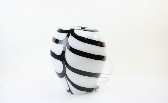 Handgemaakte lamp van wit glas in ronde vorm met zwarte strepen en inkepingen aan de bovenzijde.