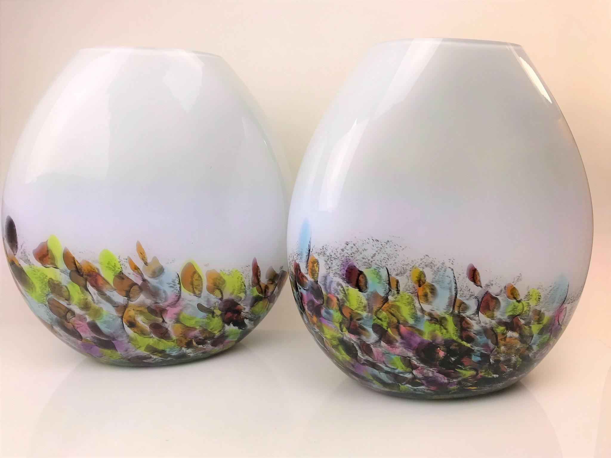 Handgemaakte lamp in ronde vorm van kleurrijk glas met opening aan de bovenzijde.