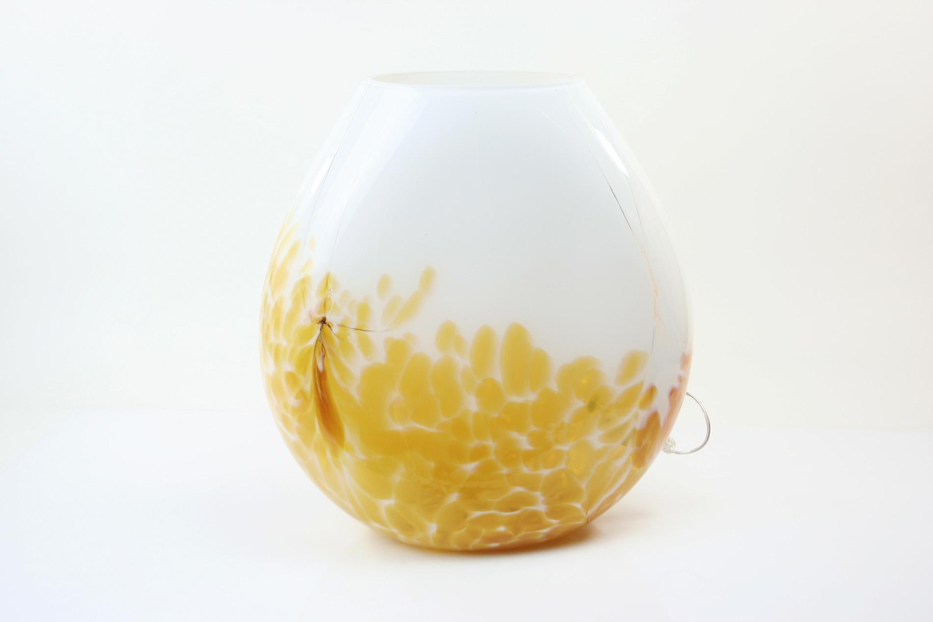 Handgemaakte lamp in ronde vorm met mooie gele accenten.