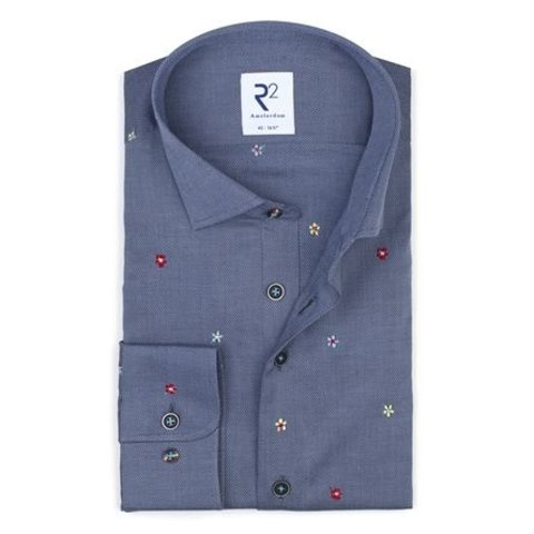 Blue cotton shirt embroidered with flowers.