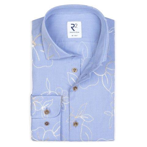Hellblaues Baumwollhemd mit Stickereidetails.