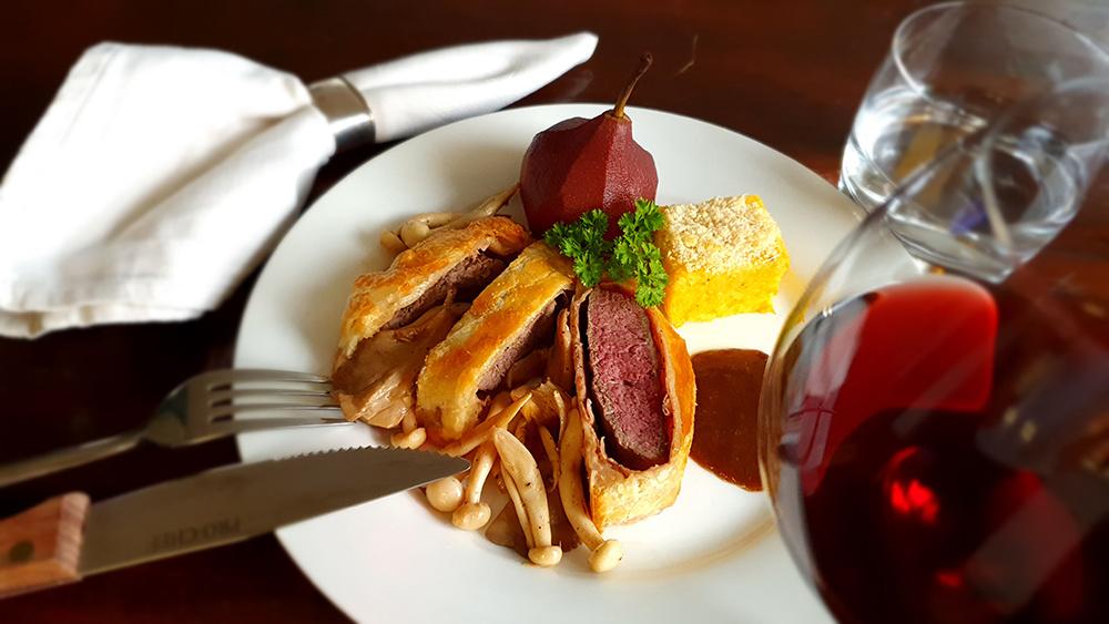Herten steak Wellington met pruimensaus, paddenstoelen, stoofpeer en polenta