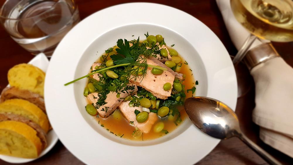 Zalmfilet in visfond met groene kruiden en sojabonen