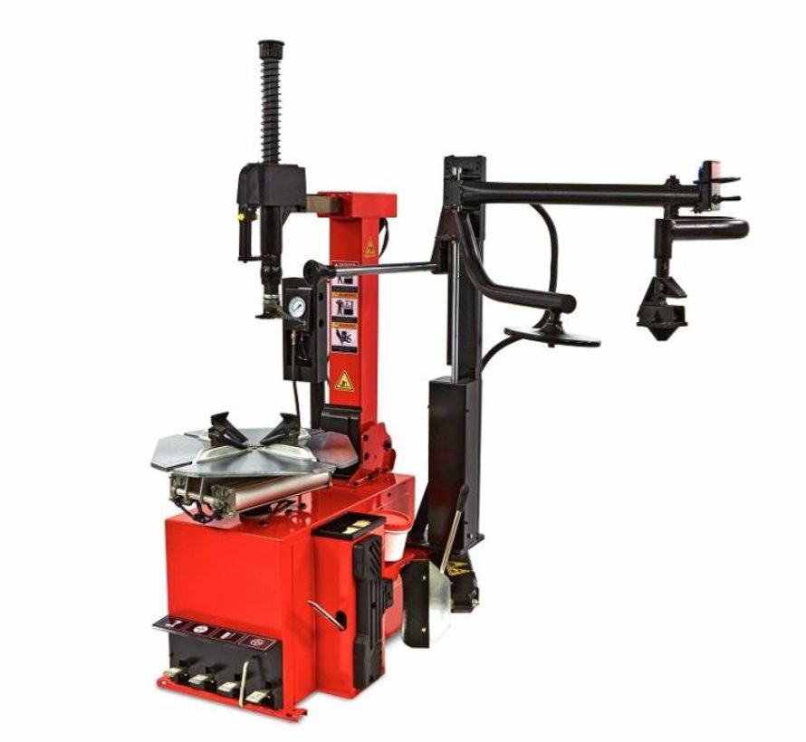 Tire dismantling machine with auxiliary arm