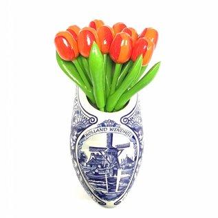 Orange wooden tulips in a Delft blue clog