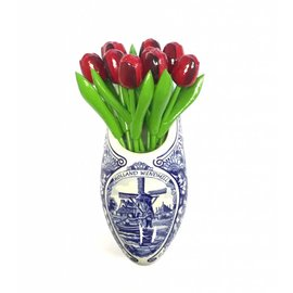 Red wooden tulips in a Delft blue wooden shoe