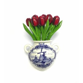 Red wooden tulips in a Delft blue wall vase