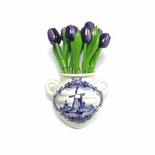 Small dark purple wooden tulips in a Delft blue wall vase