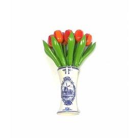 houten tulpen in de kleur oranje in een Delfts blauwe vaas