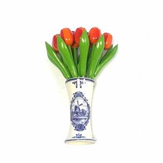 small wooden tulips in orange in a Delft blue vase