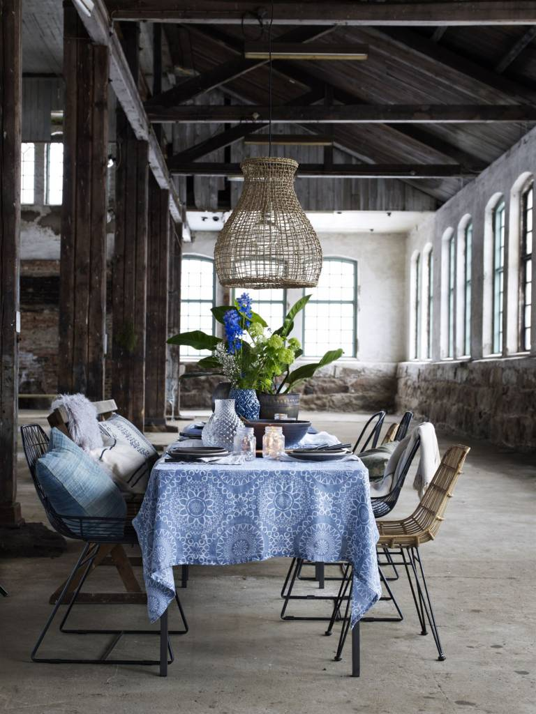 Superbe diner table setting, with a mix of chairs in iron, rattan and a wooden bench. Above the dining table a large naturel pendant lamp.