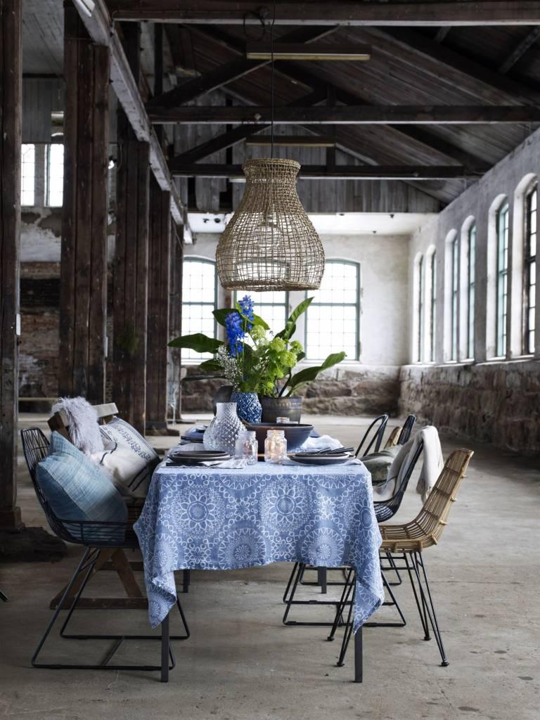 Superbe table et sa décoration, avec un mix de chaises en métal, rotin et bois. Au-dessus de la table, une suspension naturelle.