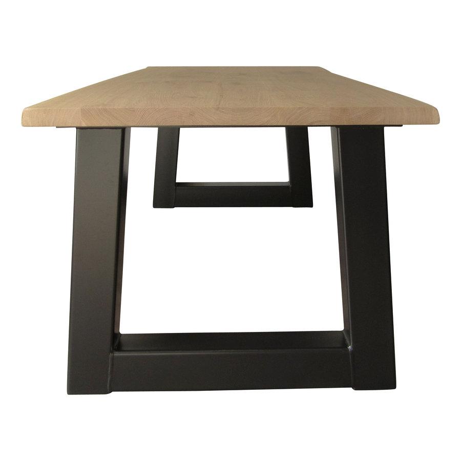 Industriële tafel voorzien van zware trapezium tafelpoten en rustiek eiken tafelblad.
