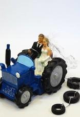 Komische bruidspaar op een blauwe tractor