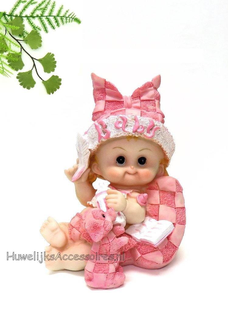 Baby meisje zit op een kussen met een baby flesje