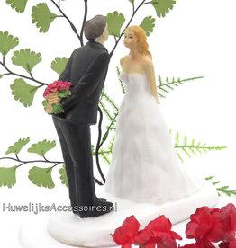 Bruidegom verbergt boeket van bruid taarttopper