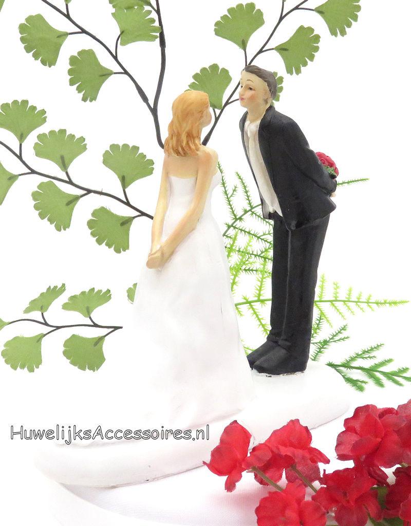 Bruidegom verbergt rozen boeket van zijn bruid taarttopper