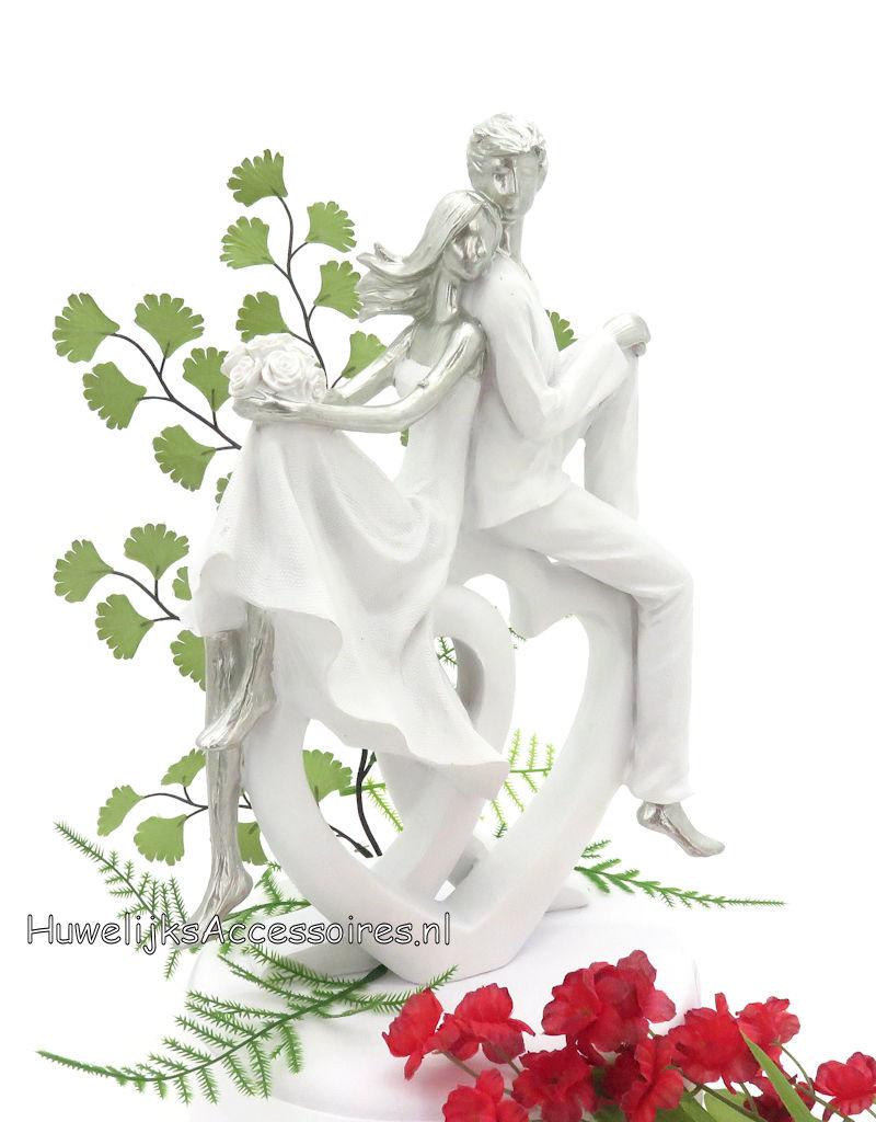 Wit & zilver bruidspaar zitten op 2 grote harten taarttopper