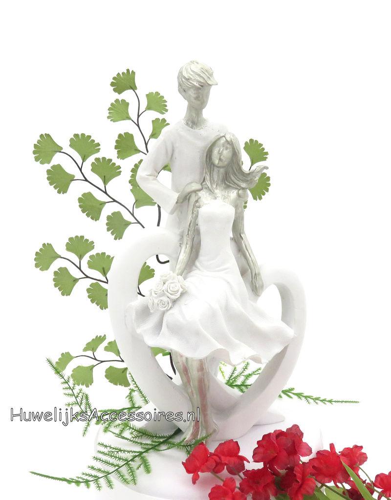 Wit & zilver bruidspaar zitten op een grote hart taarttopper
