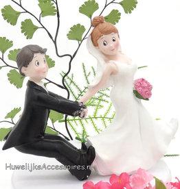 Bruid trekt bruidegom taarttopper