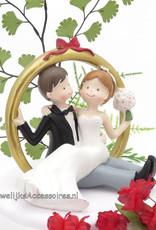 Bruidspaar zitten in een gouden ring bruidstaart topper