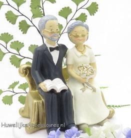 Gouden jubileum bruidspaar op een bank