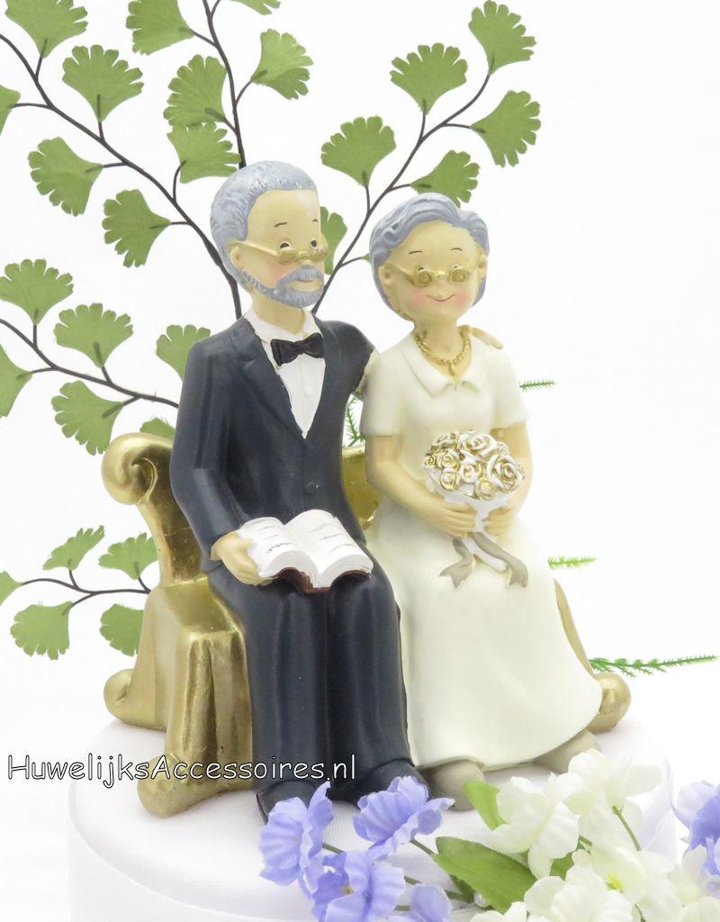 Gouden jubileum bruidspaar zitten op een bank taarttopper